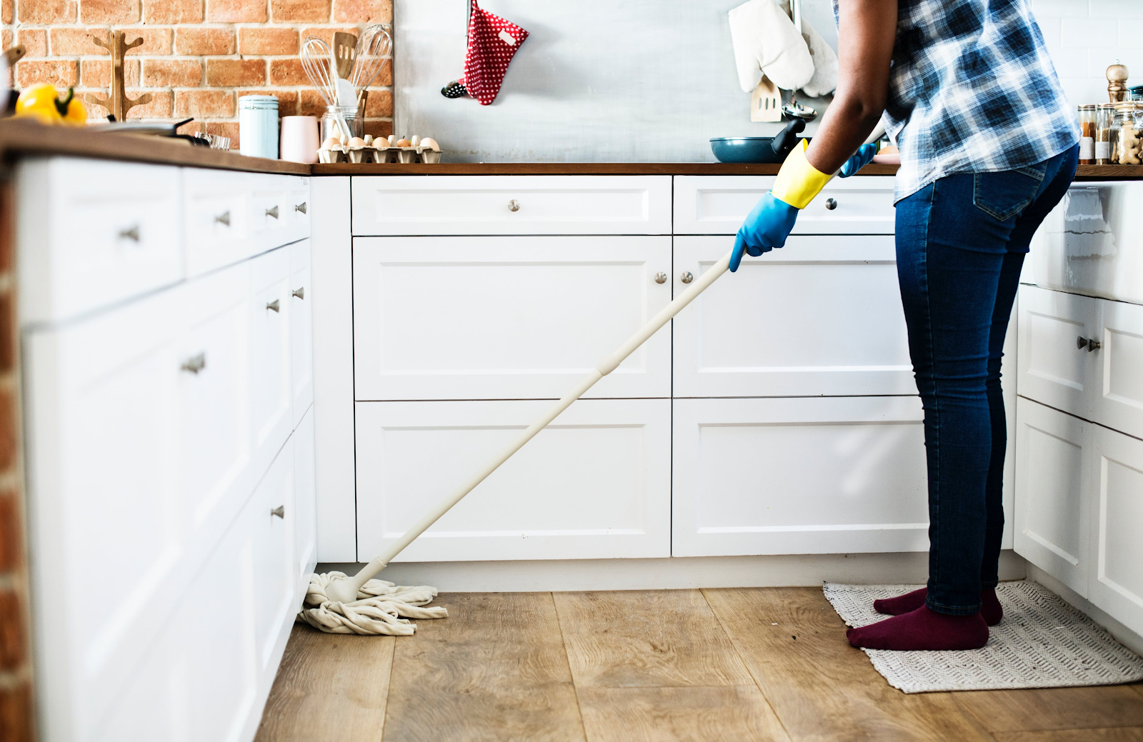 Person mopping kitchen [Image source: https://www.pexels.com/photo/person-using-mop-on-floor-1321730/]