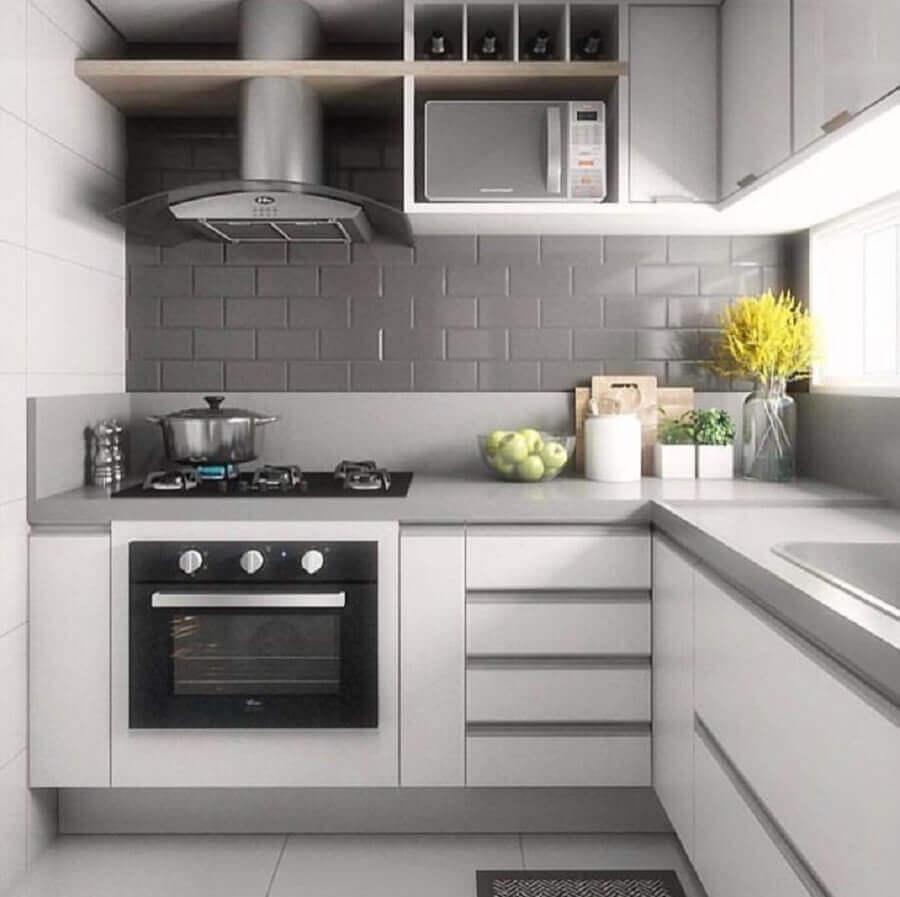 Cozinha com armários brancos e bancada cinza com piso branco e azulejo do metrô cinza.