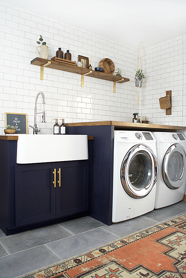 small farmhouse laundry room with navy blue shaker cabinets, large white farmhouse sink, subway tile, wood accents and tile floors