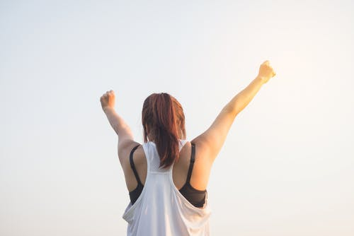 Woman Wearing Black Bra and White Tank Top Raising Both Hands on Top
