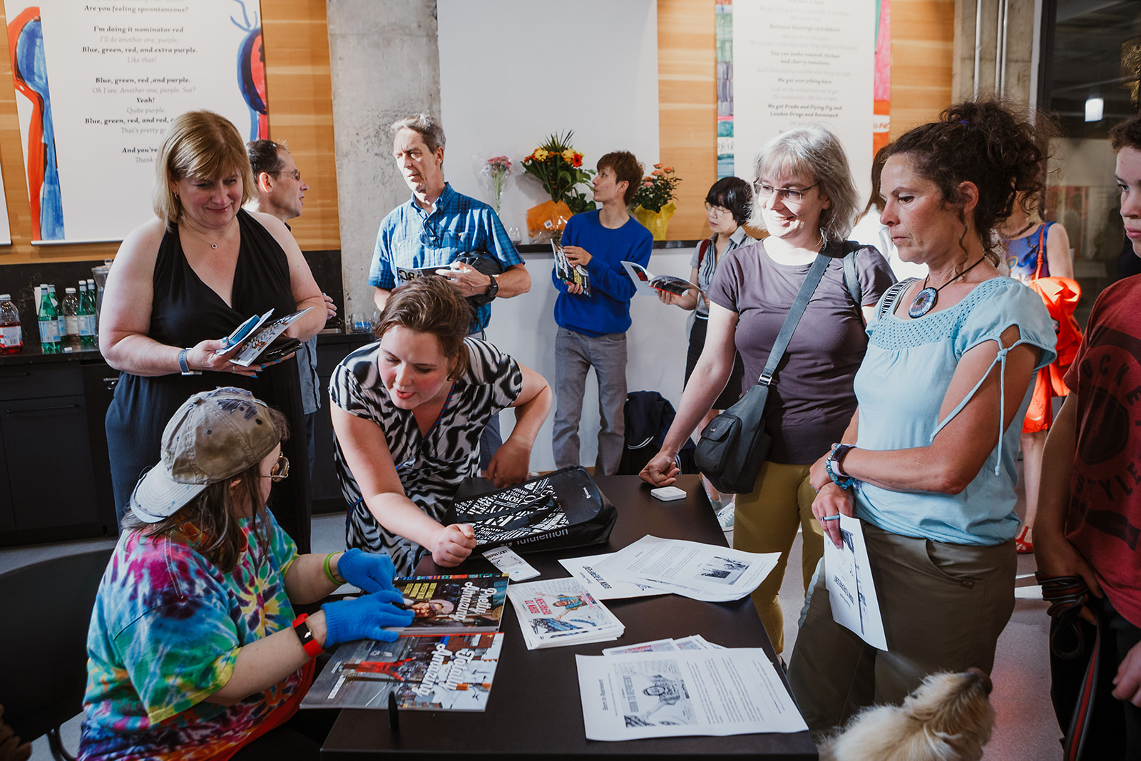 People line up to have Teresa sign copies of her books. A Spectrum Society support worker leans forward towards Teresa. Photo: This Is It Studios.