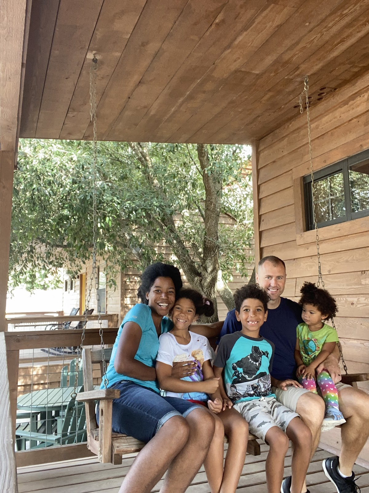 Interracial family sitting on a porch swing of a cabin which is something to remember on your family camping checklist.
