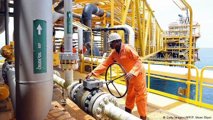 A man turns a wheel on an oil drilling platform in Port Harcourt, Nigeria