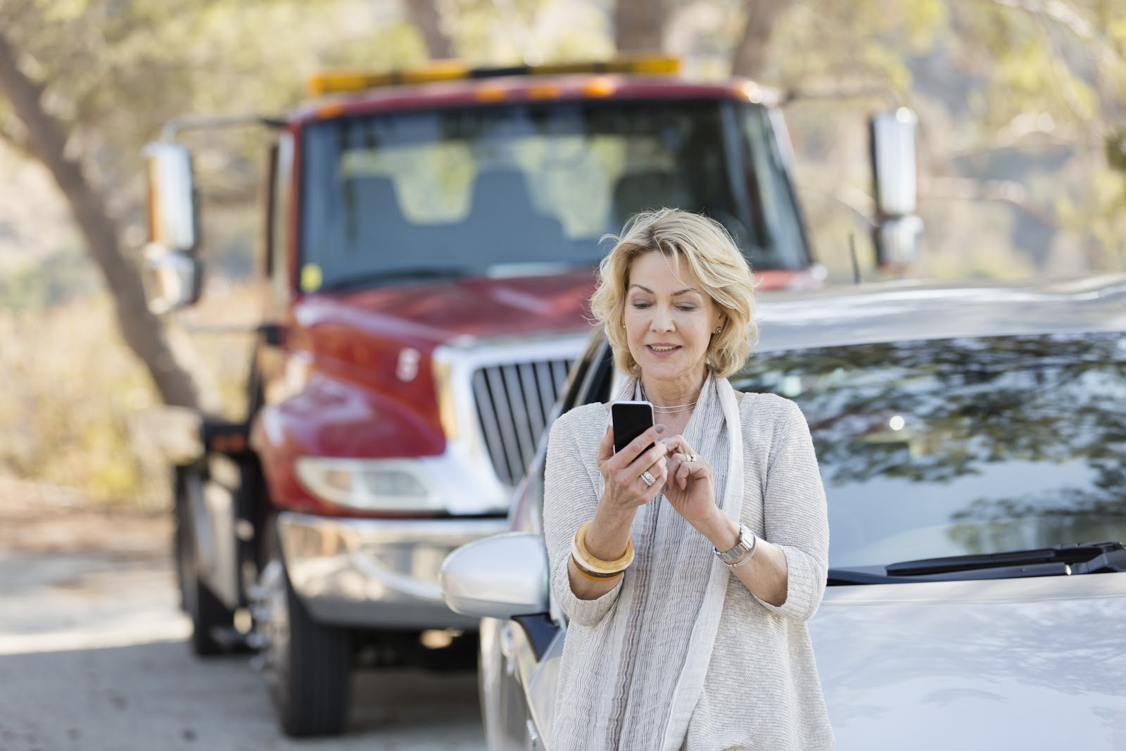 Uma mulher mexendo no celular enquanto seu carro está parado na estrada.