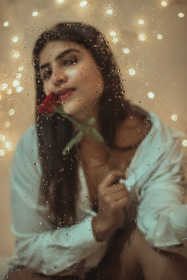 woman with rose behind glass