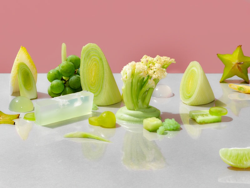 Green grapes sit next to an unripe starfruit, cauliflower stems, and amorphous jellies.