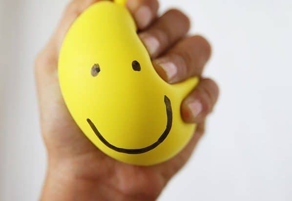 hand squeezing yellow stress ball work-related stress
