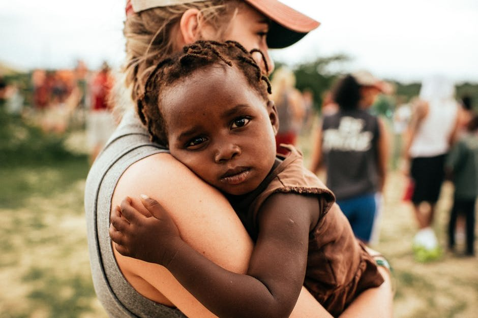 Woman on Gray Shirt Caring African Child With Gray Shirt