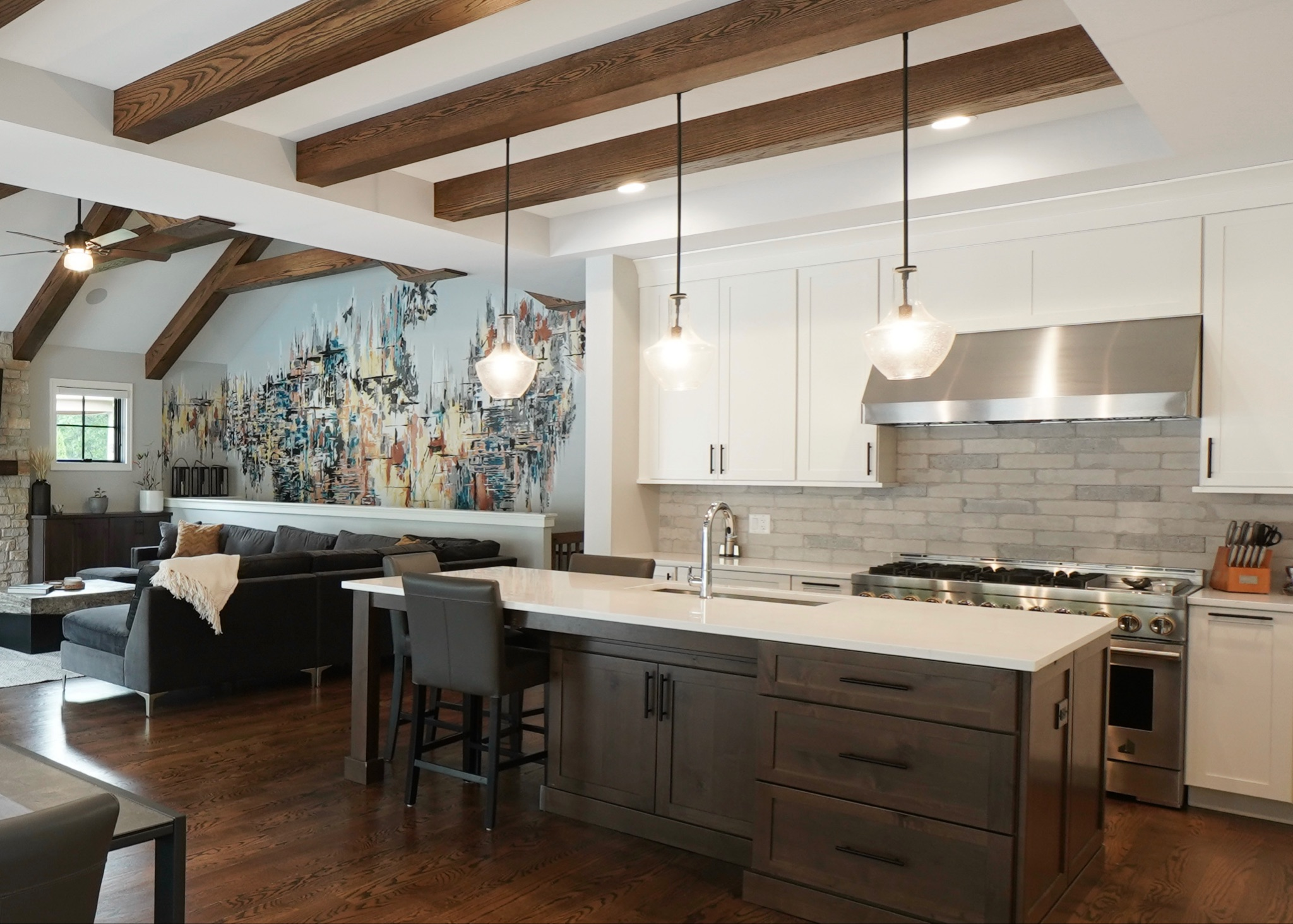 Open floor plan kitchen with a large island, natural wood beamed ceiling, featuring white and wood cabinetry, a brick backsplash and stainless steel appliances.