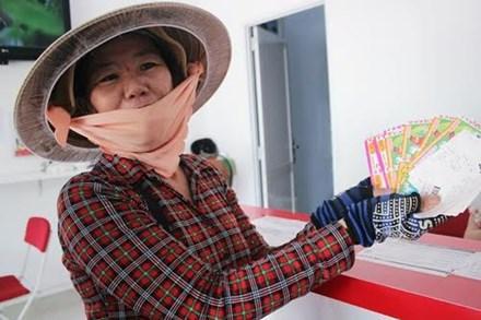 Description: Người bán dạo vé số truyền thống kèm vé số tự chọn. Ảnh: Phương Đông.