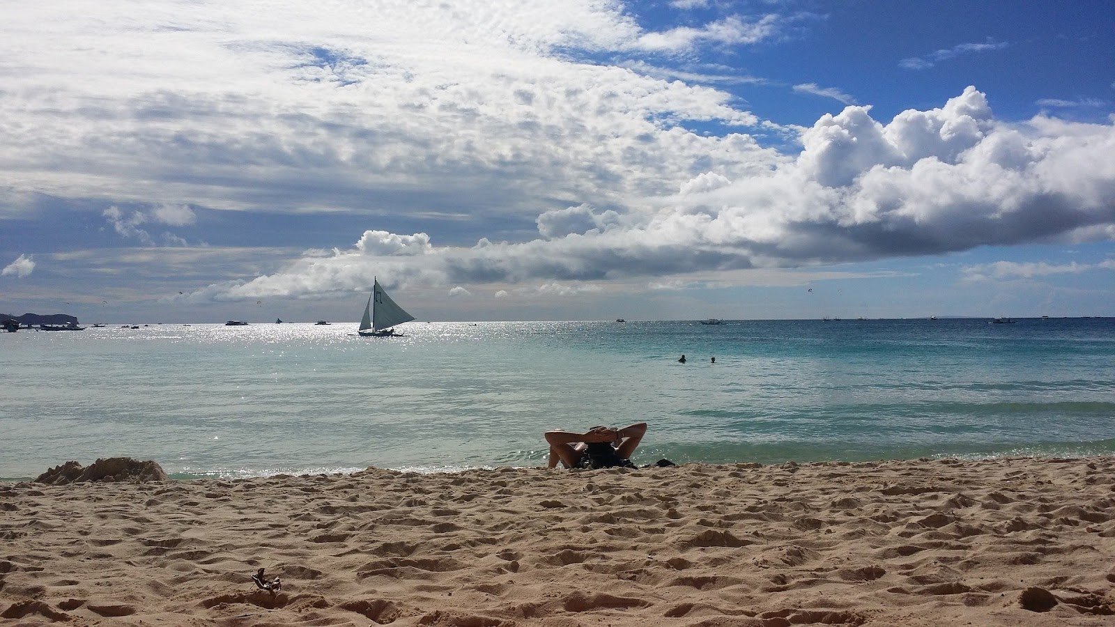 A lone person lying on a Boracay beach, with a sailboat in the distance