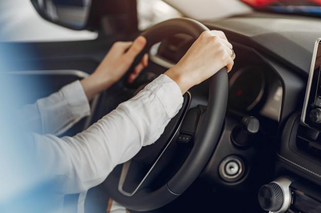 Mulher segurando com as duas mãos o volante do carro.
