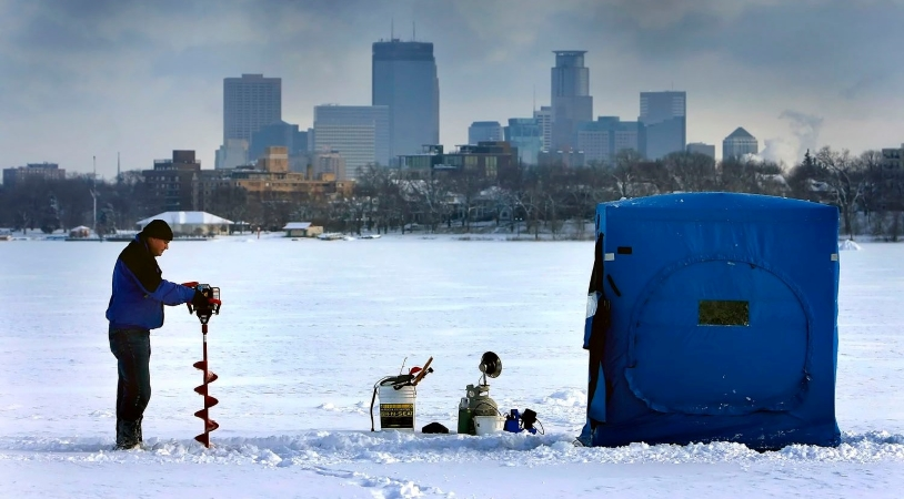 a man gets ready to do some ice fishing with Minneapolis in the background