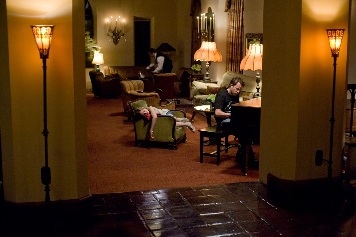 A still of an empty but well-lit interior of the Chateau Marmont. Both lamps and candles are present. An employee works in the background dressed in black and white as an exhausted Cleo is asleep in an armchair, one arm dangling over the armrest. Johnny plays the piano. It's almost like a picture within a picture, as two pillars with accompanying lamps are placed to both sides, framing the actions of the employee, Cleo and Johnny taking place in the middle.