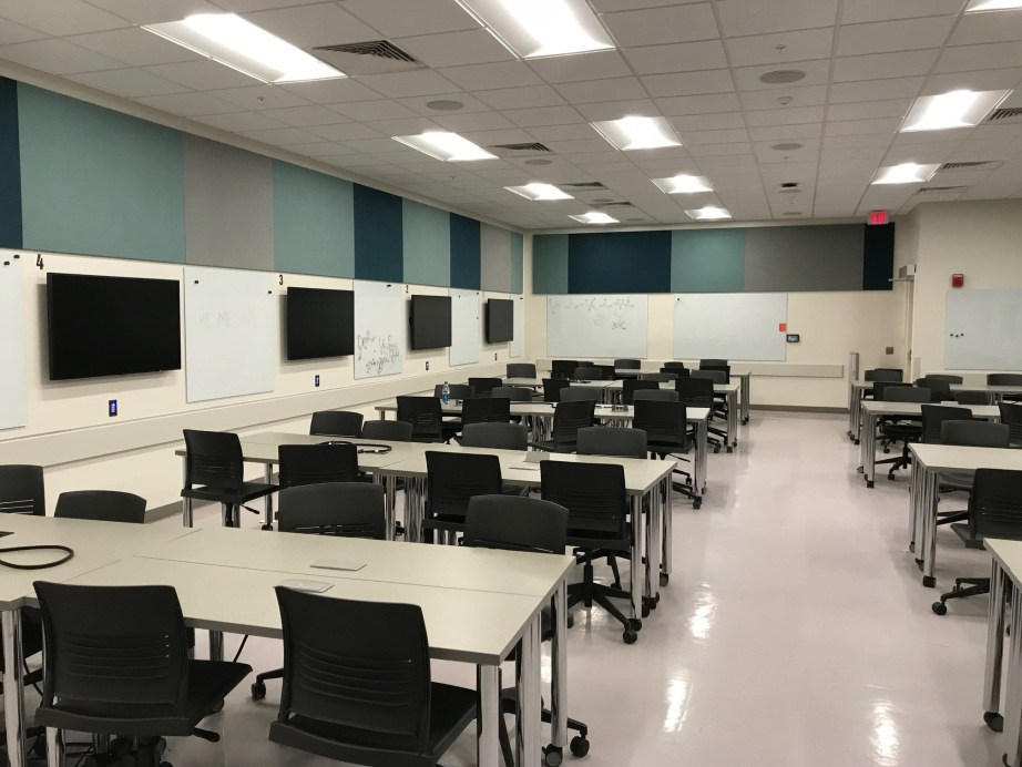 An iFLEX classroom with about 10 smaller tables for 8 people each. Each table has a flatscreen mounted on the wall next to it.