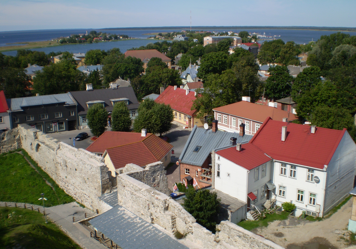 haapsalu cute white buildings with red roofs, seen from haapsalu castle. City view, surrounded by trees and baltic sea in the background.