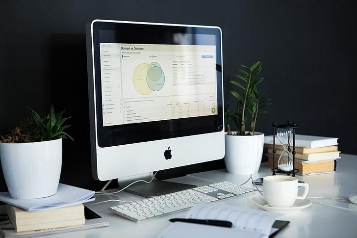 silver iMac near the white keyboard and a cup of coffee