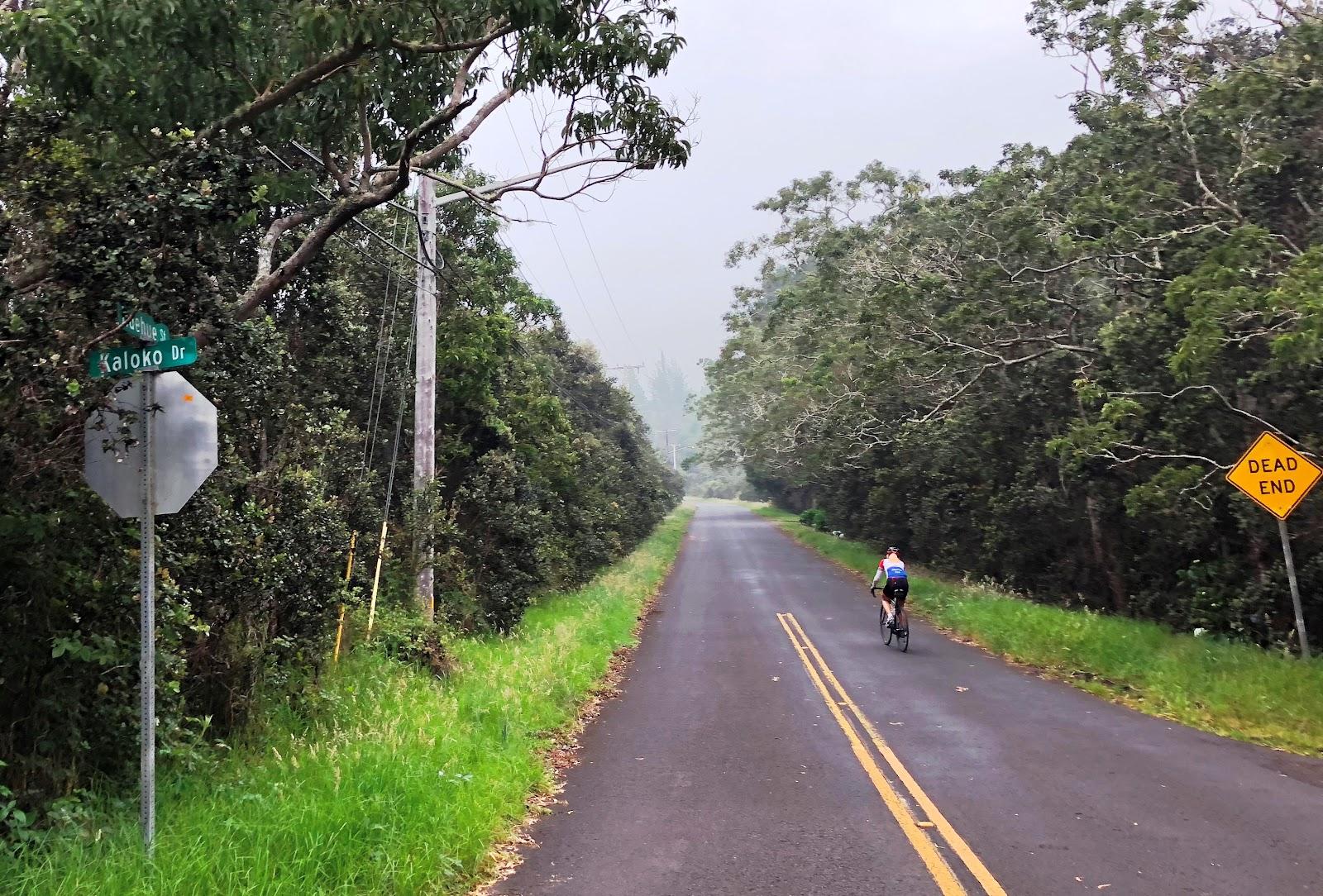 Huelue Street sign with cyclist climbing volcano on Kaloko Drive bike climb.