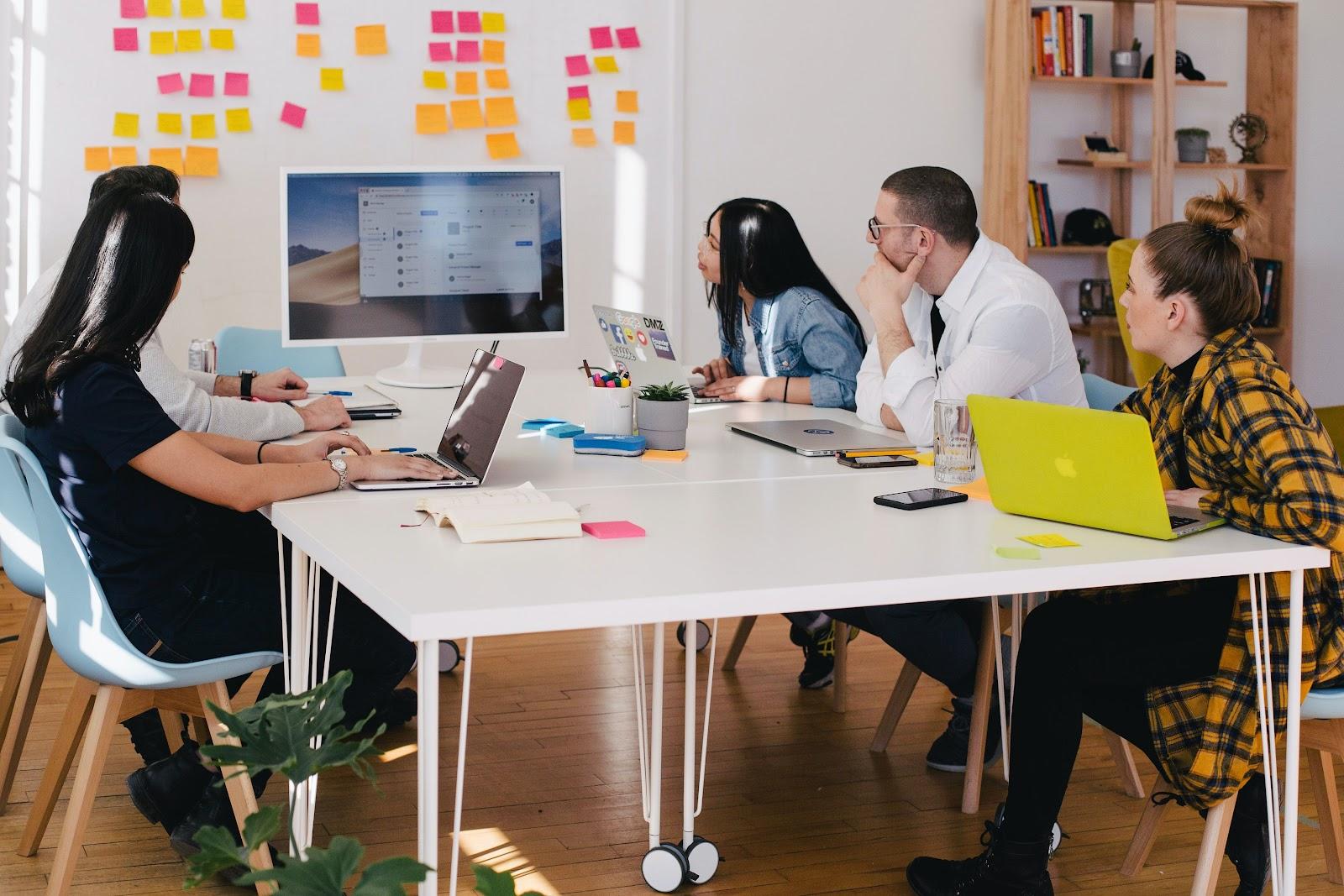 Várias pessoas em uma mesa de escritório observando um computador.