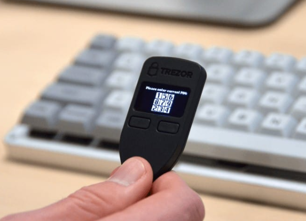 Photo of a Trezor One held in hand to illustrate the idea of how to set up the Trezor Model One.