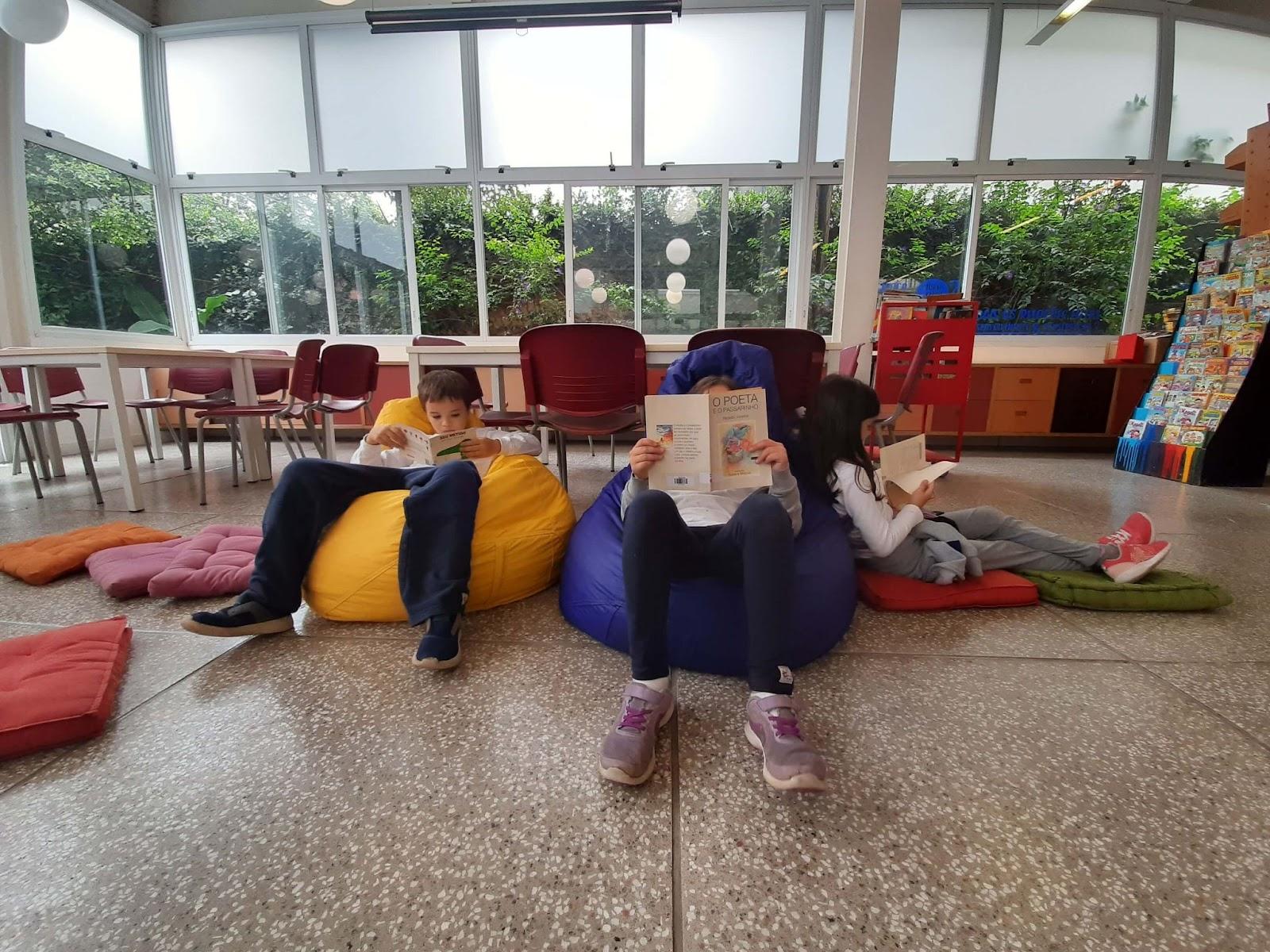 A imagem mostra três crianças sentadas em puffs coloridos lendo.