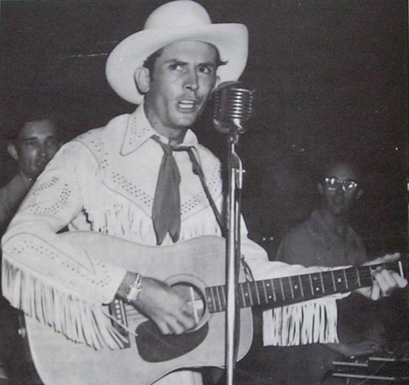 Hank Williams singing and playing the guitar.