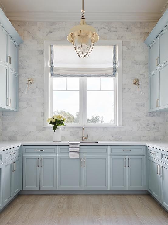 pastel blue shaker cabinets with light wood floors and grey tile backsplash
