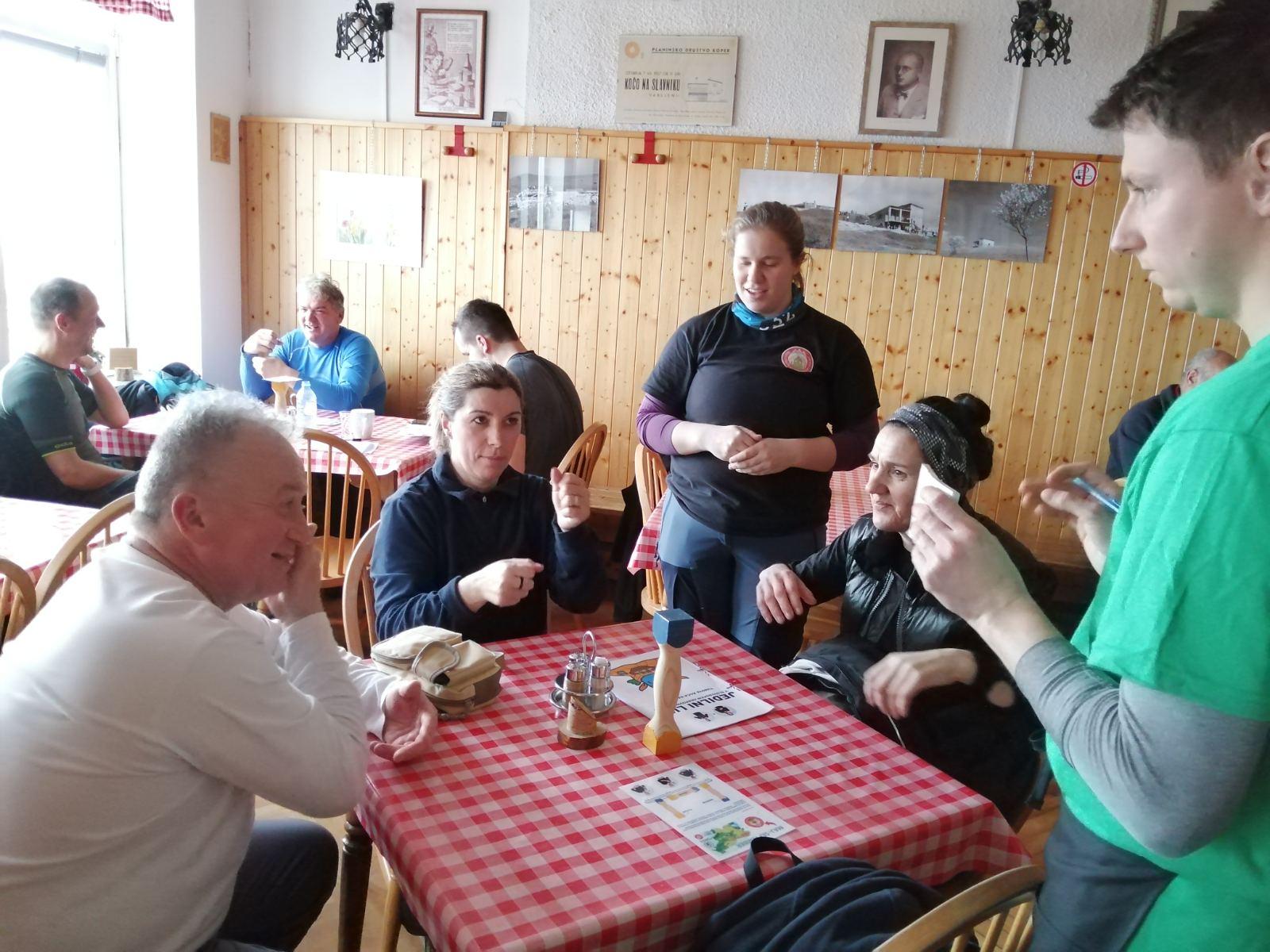 Na sliki prostovoljec Matija prejema naročilo v znakovnem jeziku. Pomaga mu tudi prostovoljka Martina. Valjček na mizi, ki je obrnjen z modro navzgor sporoča, da želijo gostje naročiti, foto arhiv GSPK