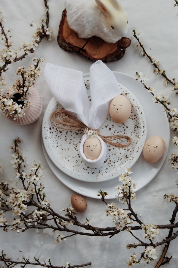 Um prato com três ovos que tem rostinhos desenhados, um deles com orelhas feita de pano ao lado de flores brancas vintages