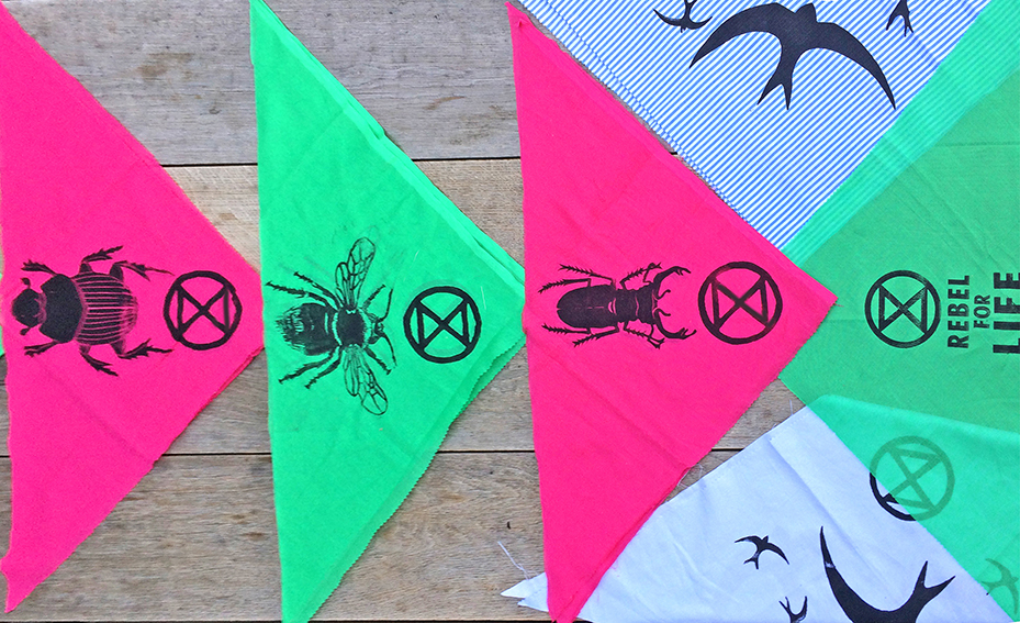 Green, pink, and blue bandannas printed with birds, beetles, bees, and the Extinction Symbol.