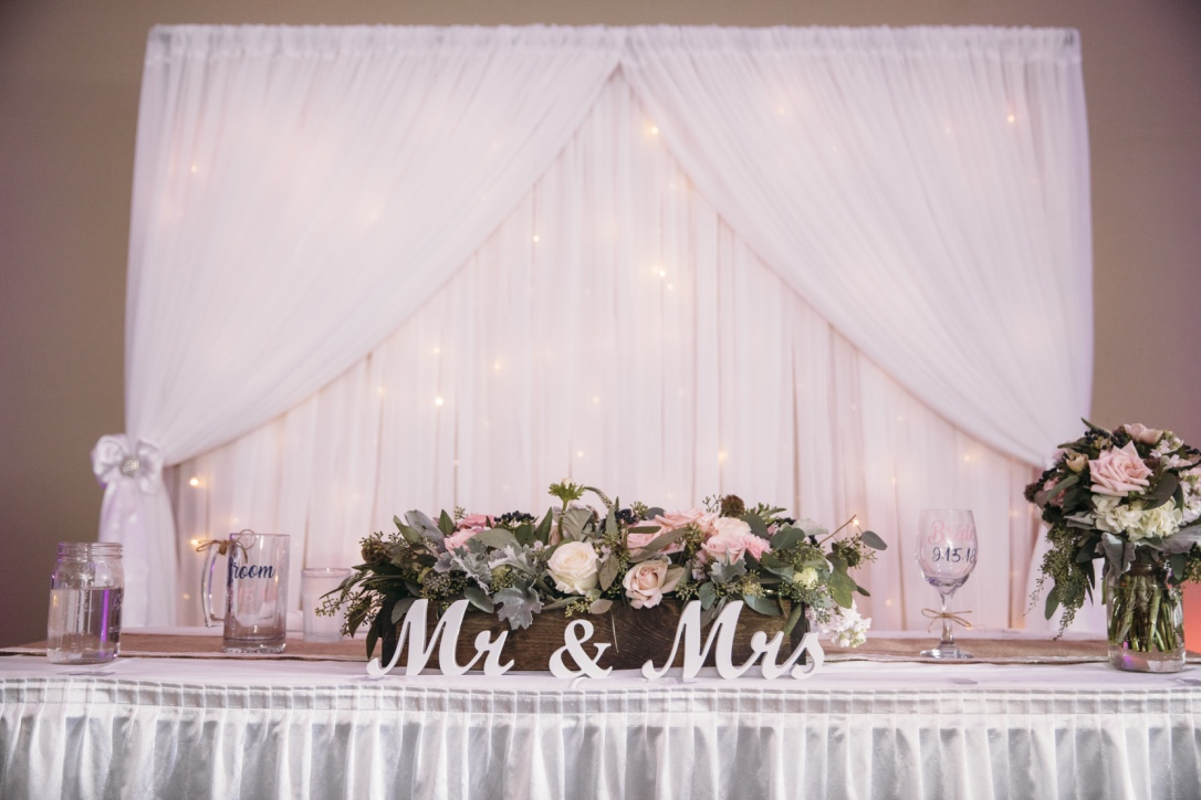 Head table setting with Mr & Mrs sign, floral arrangement and white tulle drapery and fairy lights backdrop.