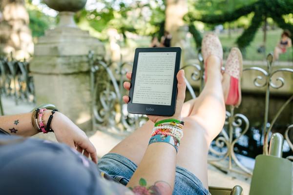 foto de uma mulher sentada lendo um kindle