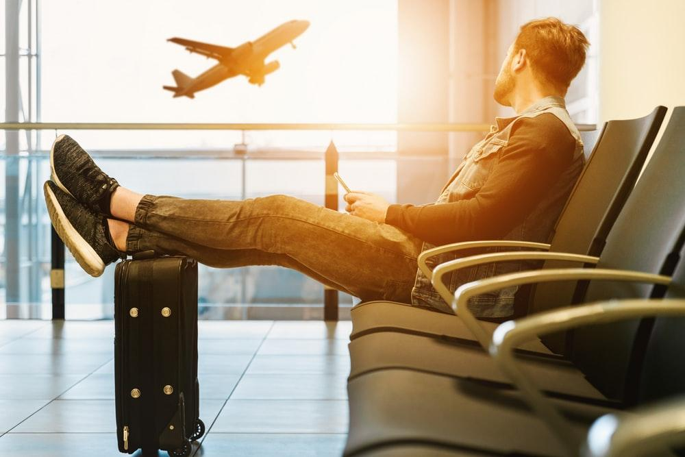 man sitting on gang chair with feet on luggage looking at airplane