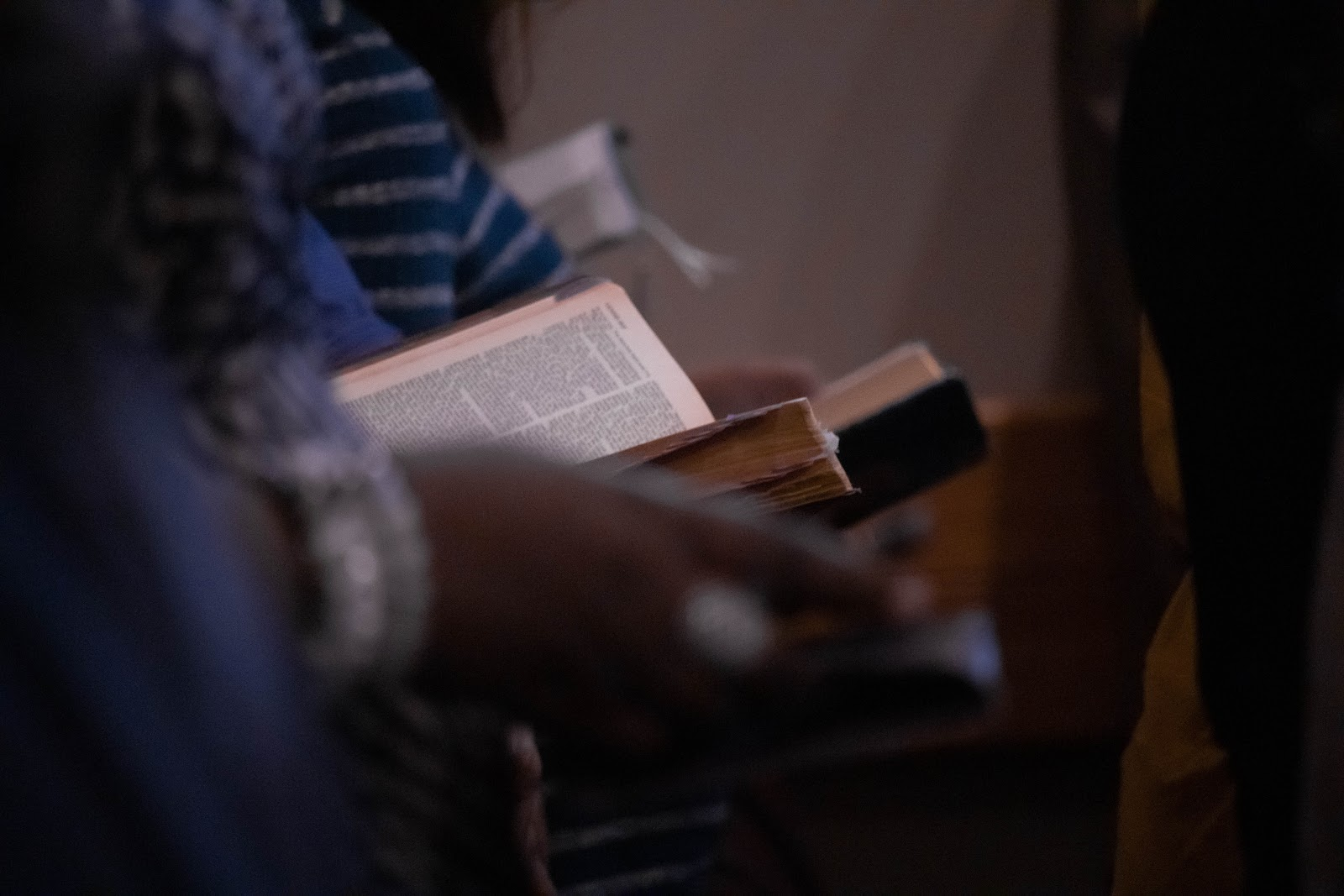 A row of people holding Bibles.
