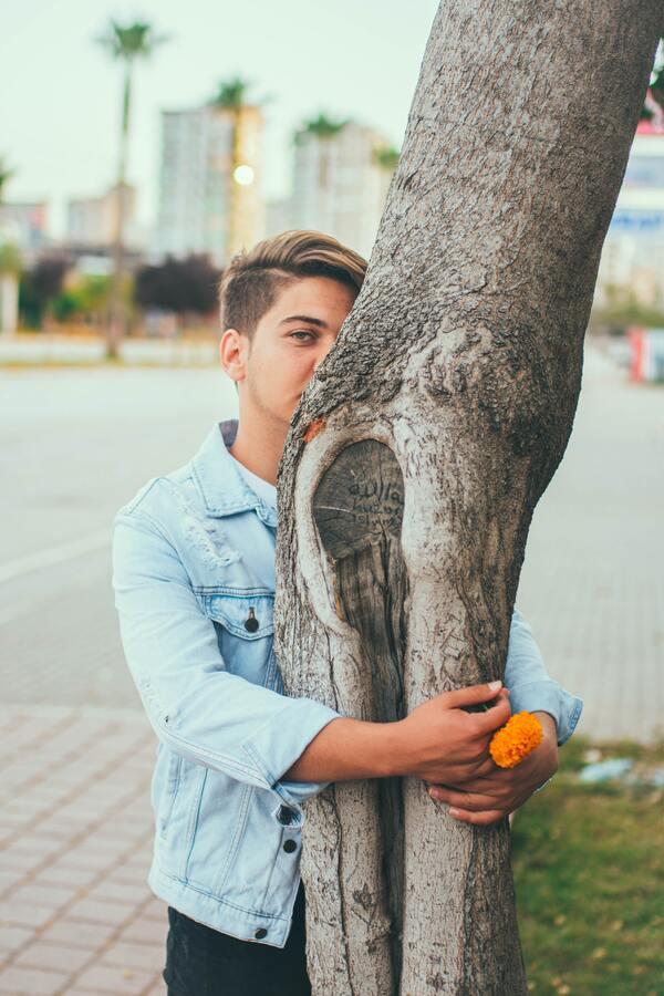 homem abraçando uma árvore e sgurando uma flor