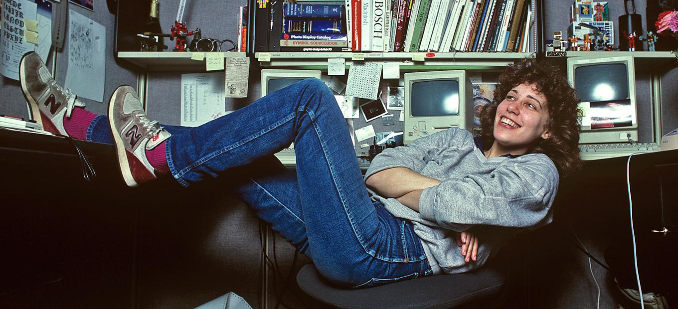 Photo of Susan Kare, one of the women in design featured in our article, legs up at her cubicle at Apple