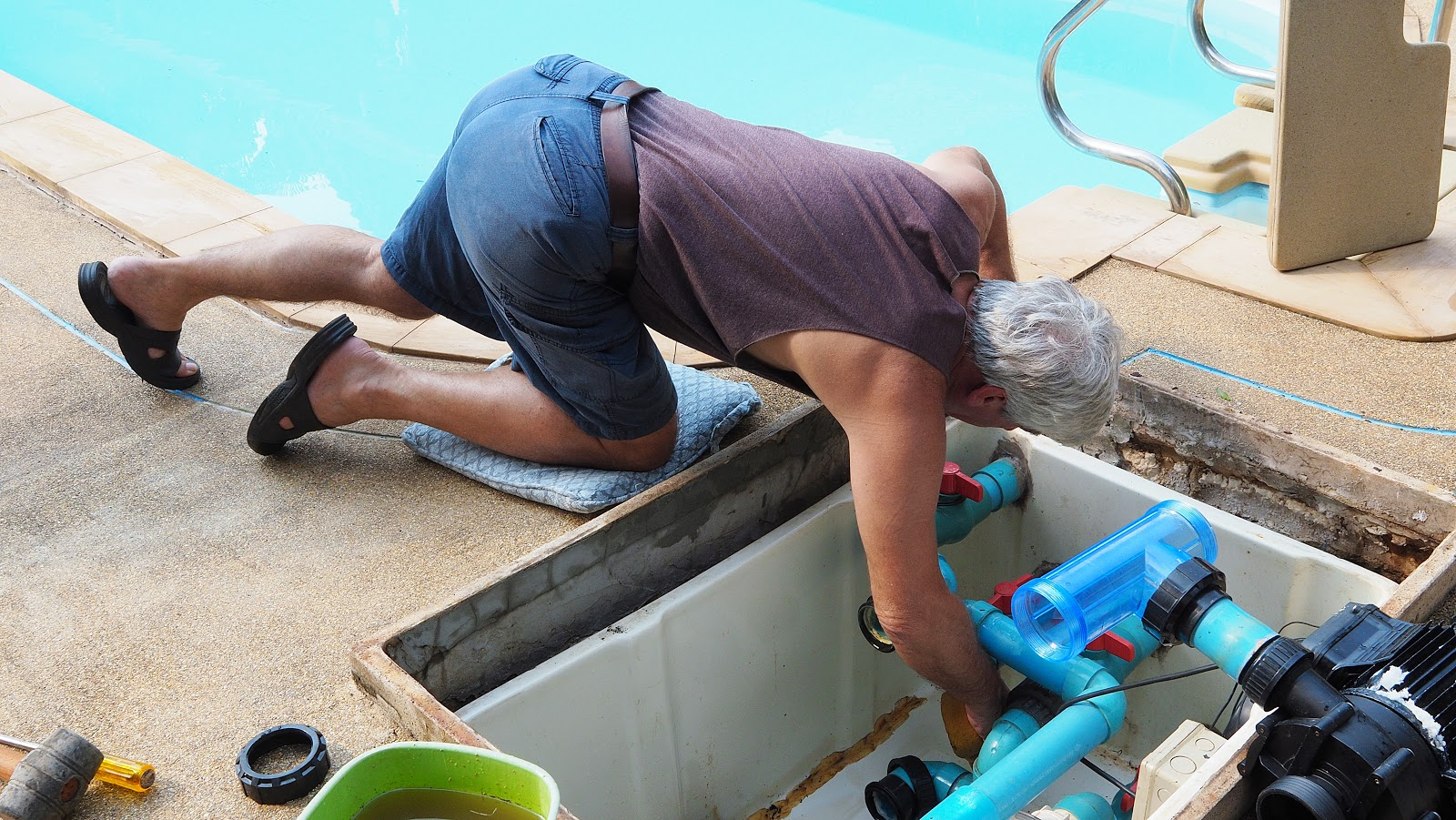 a man finding a leak in an inground swimming pool pipe