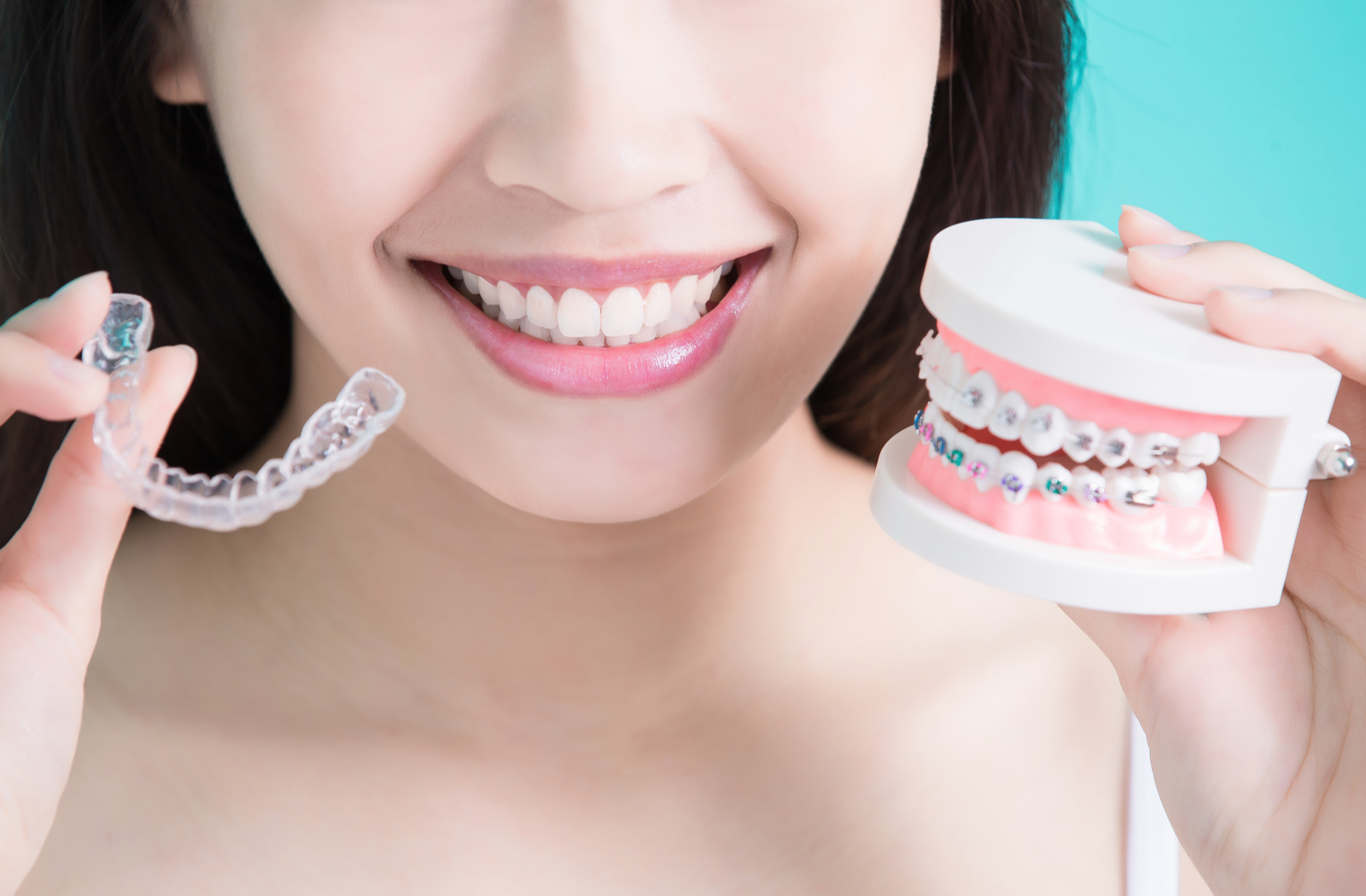 woman smiling holding an Invisalign aligner in one hand and a model of teeth with braces on them in the other