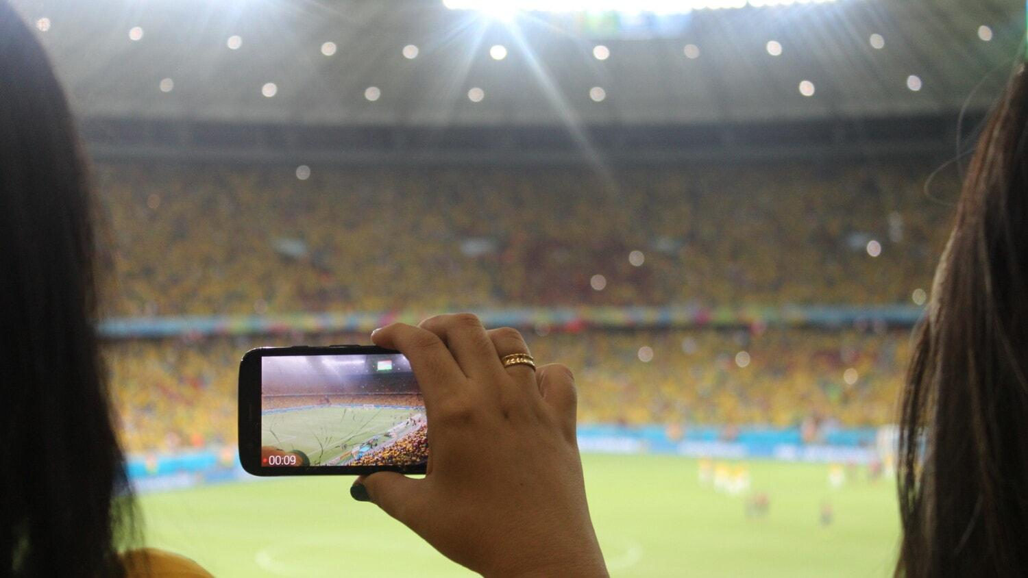 fans recording match with phone in a stadium
