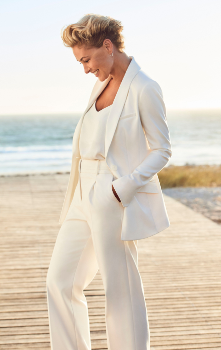 A woman, Emma Willis, stands on a beach in a white tailored blazer and trousers