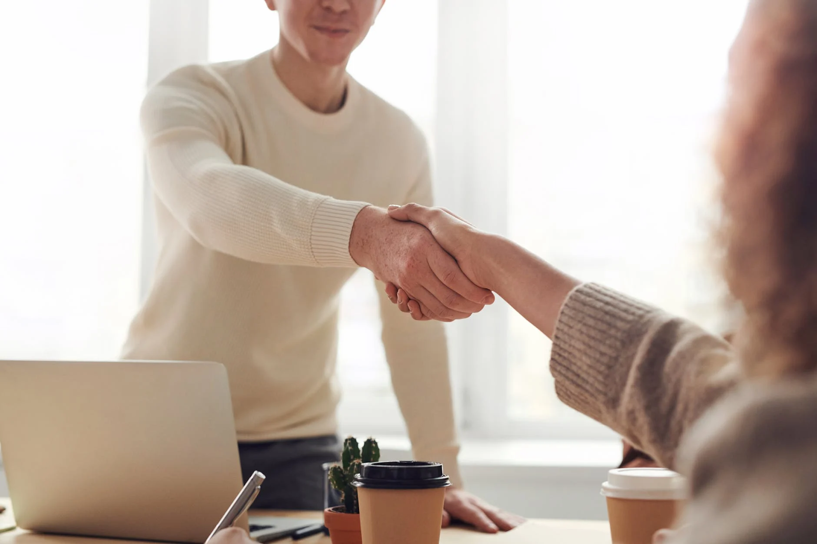 man-and-woman-near-table-hand shake avoid common business pitfalls