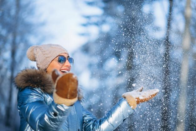 Woman blowing snow from gloves Free Photo