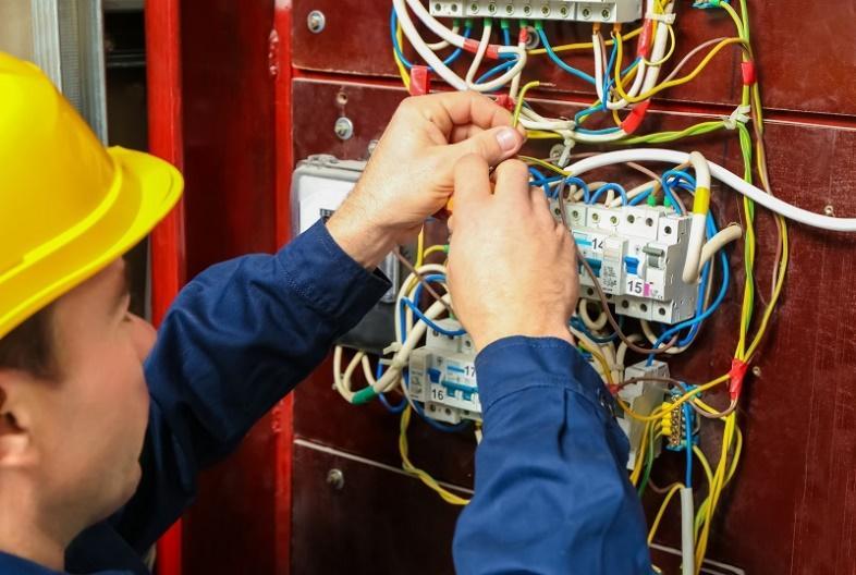 homem-com-vestimenta-contra-eletricidade-enquanto-mexe-em-alguns-fios