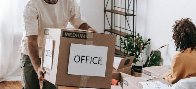 A man holding a moving box labeled 'office'