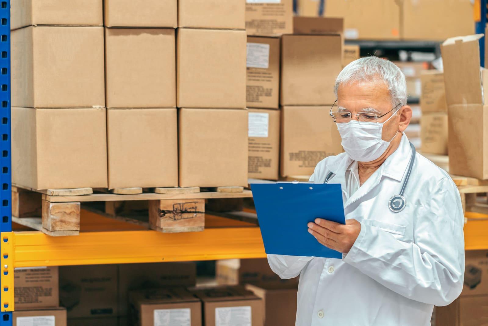 A imagem mostra um farmacêutico operando o estoque de uma distribuidora de medicamentos.