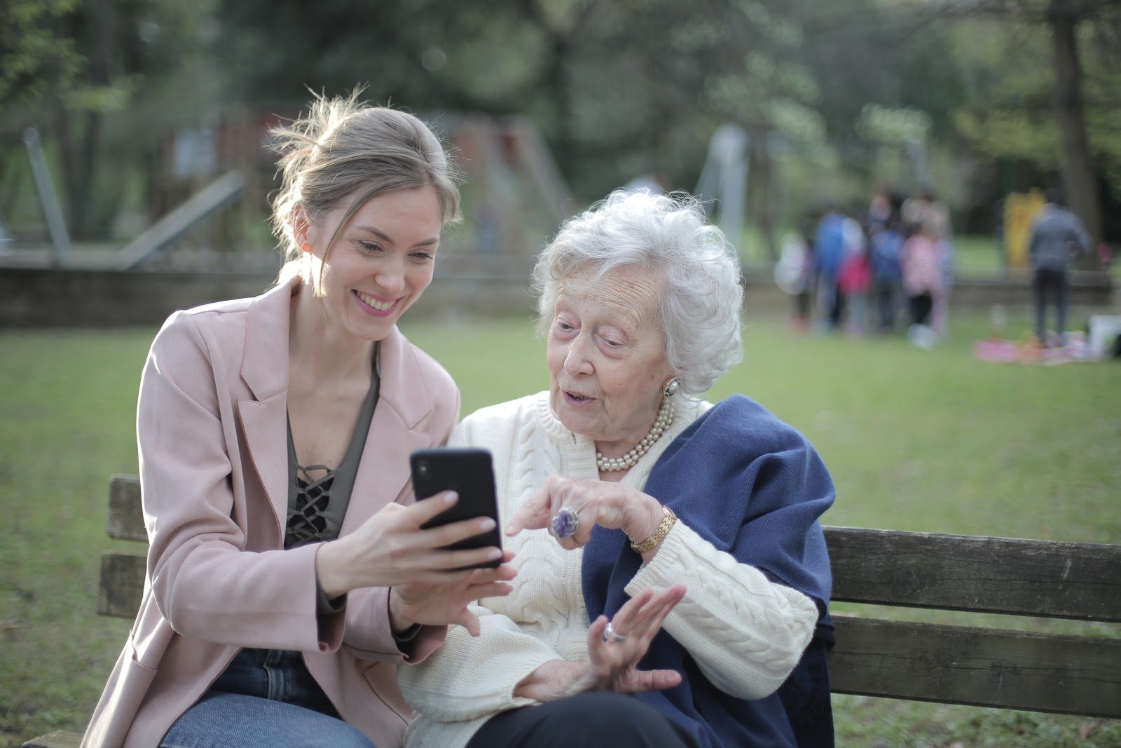 A young woman helping an elderly woman with technology to deal with anxiety