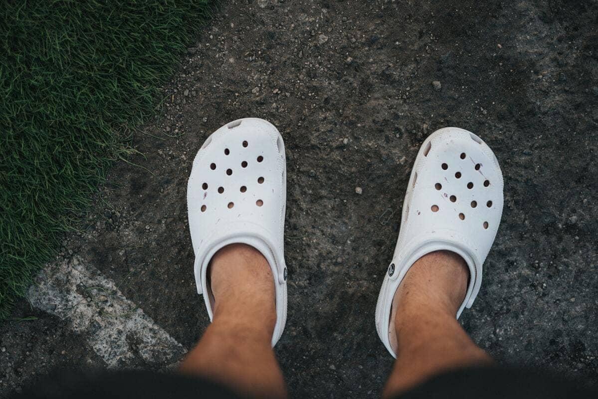 Dei piedi di un ragazzo che indossa delle ciabatte crocs bianche su una spiaggia nera
