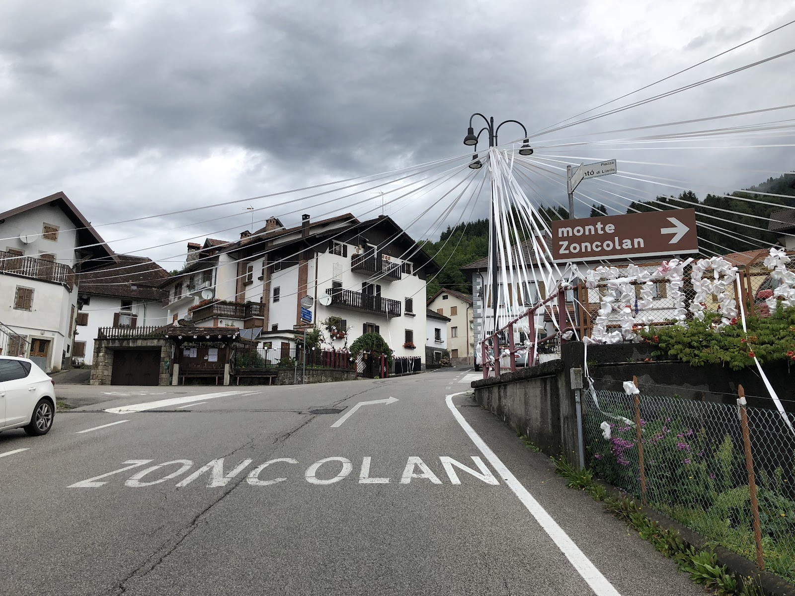 bike climb of Monte Zoncolan from Ovaro - start of climb - town, buildings, road and sign