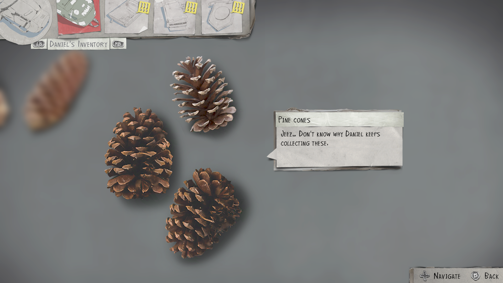 "An inventory screen. Three pine cones are in focus, with a label that looks like a paper cutout of a speech bubble that reads: ""Pine cones. Jeez... Don't know why Daniel keeps collecting these."" The text is not very big."