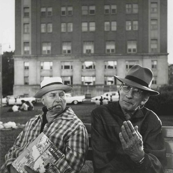 A black and white image of 2 men sat on a bench having a discussion by Vivian Maier